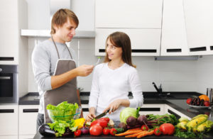 Couple discussing meal preparation surrounded by produce in a modern airy kitchen